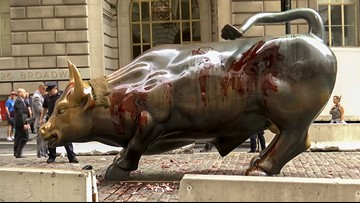Climate activists pour fake blood on Wall Street bull statue