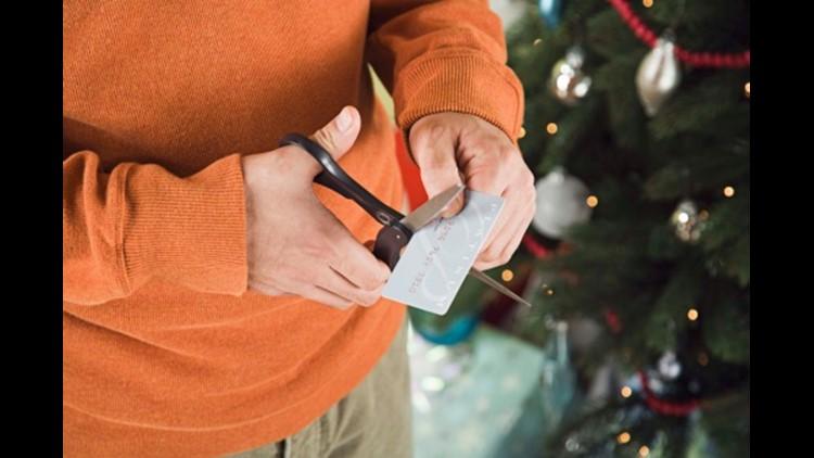 Man cutting credit card with scissors. Photo: Thinkstock