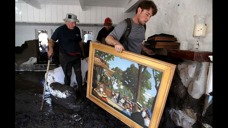 Robert Drenic carries a painting the home of a family member that was destroyed by a mudslide on January 11, 2018 in Montecito, California.