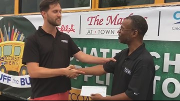 Fuccillo Automotive Group giving $5,000 check to United Way during Stuff the Bus