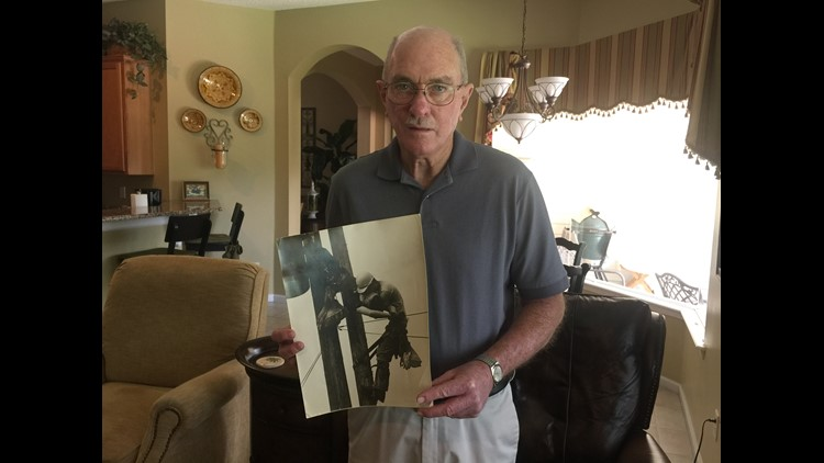 "J.D. Thompson holds iconic ""Kiss of LIfe"" photo that captured him saving a fellow electrical lineman's life in 1967 (PHOTO: FIrst Coast News)"